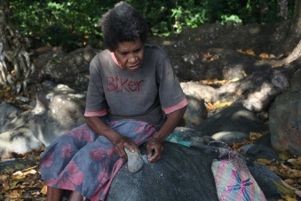 Aunty Ebwu demonstrating the techniques for grinding down the shells by hand. (Gina Kaitiplei)